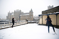 UK Weather: Heavy flurries of snow fall in Aberystwyth, west Wales,  on a cold February morning in Aberystwyth, west Wales, UK. Tuesday 06 February 2018.  Three Aberystwyth universuity students have a snowball fight, with the iconic Old  College building behind them in the snow<br /> The Met Office has issued a 'yellow' warning for snow and ice, as a band of sleet and snow moves in from the west, to cover much of Wales and the north of England