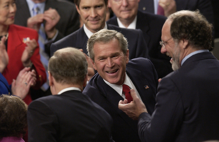 President George W. Bush smiles and greets Democrats  after his State of the Union address.