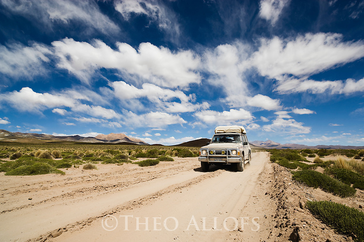 Bolivia, Altiplano, 4x4 vehicle on dirt track crossing Altiplano grassland, storm clouds