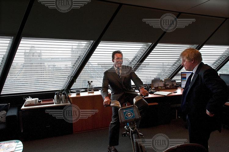 Arnold Schwarzenegger sits on a Boris bike as he meets Mayor of London Boris Johnson at City Hall, London.