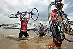 From left, Maddie Nelson and Kelli Pryde, both of Glen Ellen, Ill.,  and David Butler of Barrington, Ill., march with their bikes in the Mississippi River at the end of their ride in Dubuque Saturday on RAGBRAI XXXVIII.
