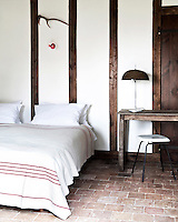 A half-timbered wall is a feature of this simple double bedroom
