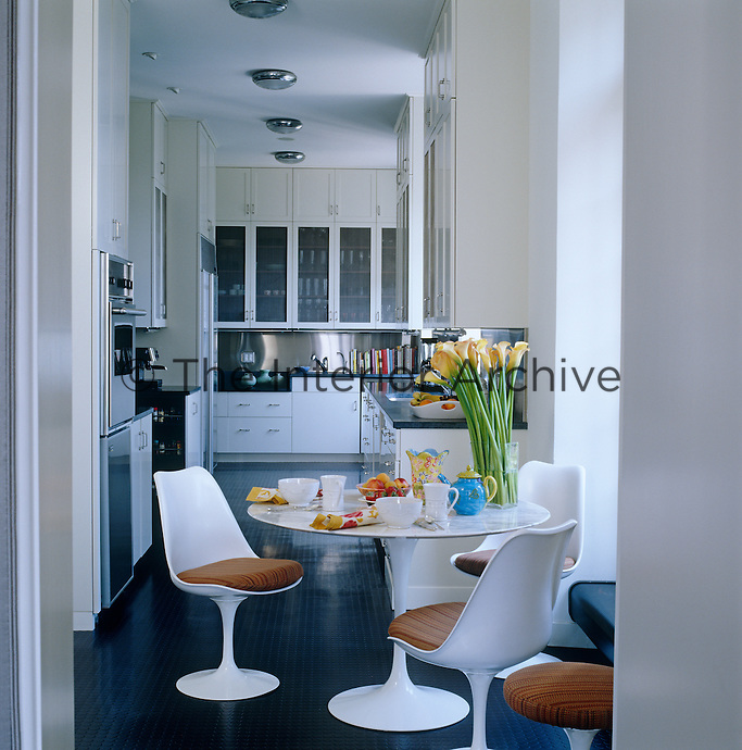 In the kitchen the classic white Saarinen Tulip table and chairs stand out against a contemporary black rubber floor