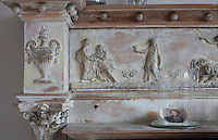 Close-up of the distressed paintwork on the carvings on the living room fireplace