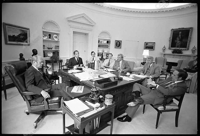 President Gerald Ford in the Oval Office with his advisers, including Chief of Staff Dick Cheney (right). The White House, Washington, D.C., USA, May 1976.
