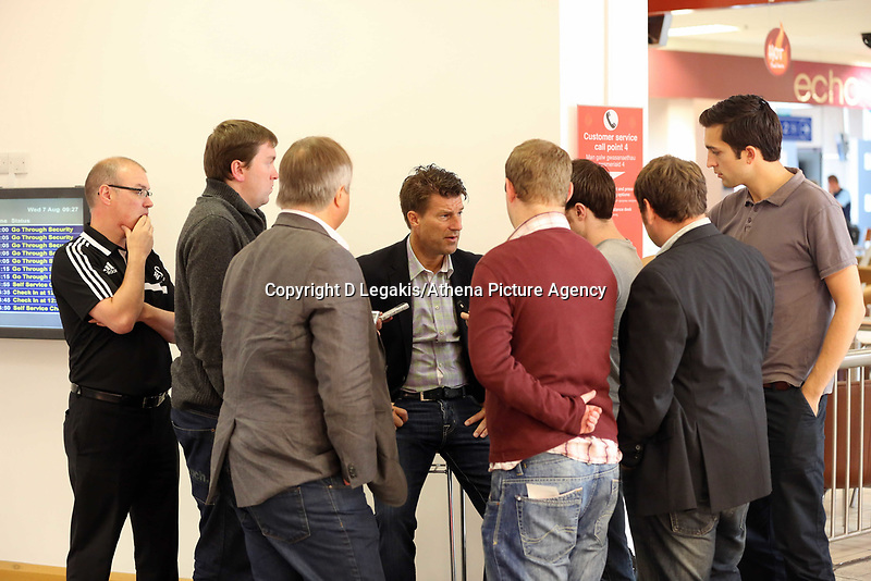 Wednesday 07 August 2013<br /> Pictured: Michael Laudrup (C) gives a brief interview to the media at Cardiff Airport.<br /> Re: Swansea City FC travelling to Sweden for their Europa League 3rd Qualifying Round, Second Leg game against Malmo.