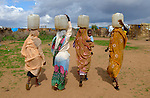 Women carry water home from a communal well in the Hassa Hissa Camp for internally displaced persons in West Darfur. Water is a key element in the conflict in Darfur, where over 400,000 people have died and some 2.5 million have been displaced.