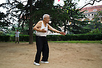 An old man practices Tai Chi in a park in front of the former headquarters of the German Administration. The building is still used by the Chinese authorities and now serves as the city hall.