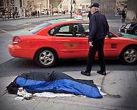 A homeless man sleeps on Queens avenue in downtown Toronto April 19, 2010.