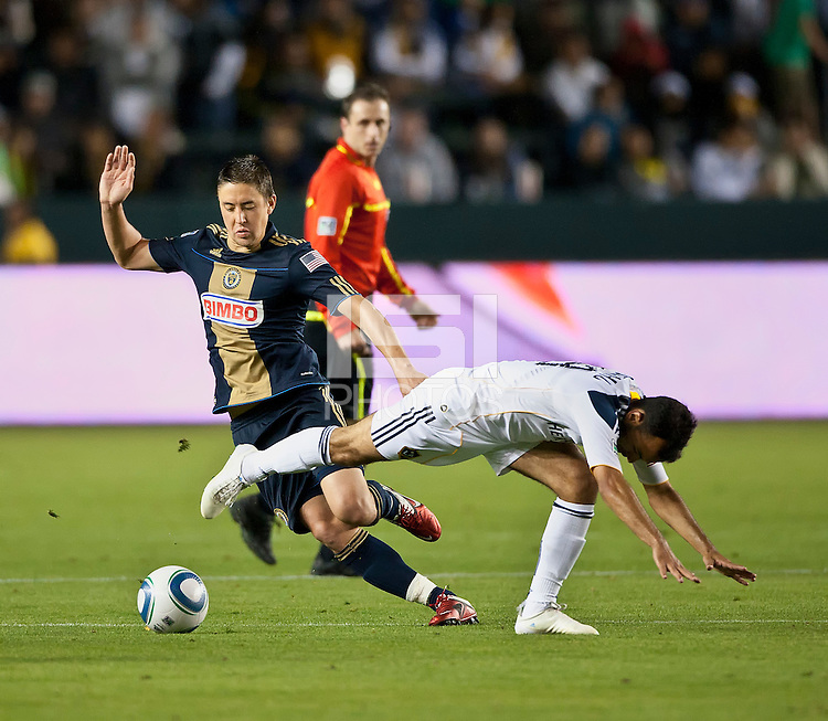 CARSON, CA – April 2, 2011: Philadelphia Union midfielder Kyle Nakazawa (13) moves the ball past LA Galaxy midfielder Juninho (19) during the match between LA Galaxy and Philadelphia Union at the Home Depot Center, March 26, 2011 in Carson, California. Final score LA Galaxy 1, Philadelphia Union 0.