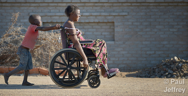 Delina Nleya gets a push from her son Nkosikhona, 7, on the street near their house in Bulawayo, Zimbabwe. Nleya suffered a spinal cord injury and uses a wheelchair provided by the Jairos Jiri Association with support from CBM-US.