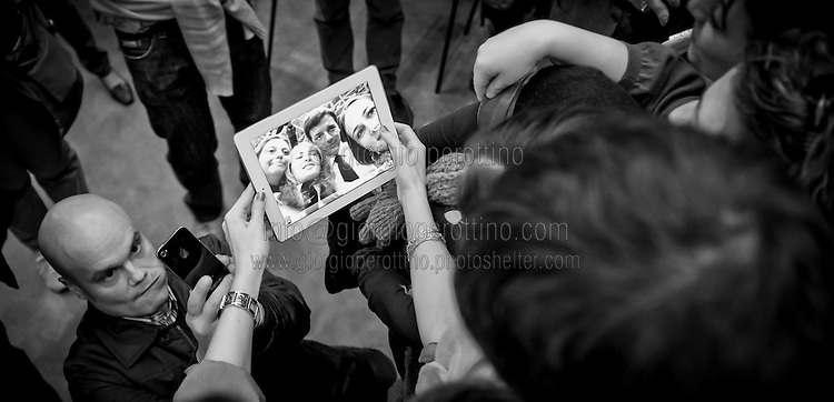 Matteo Renzi takes a selfie with some supporters using an ipad during his political campaign convention for the Partito Democratico's primary elections -Italian left wing Party - in Turin, October 21, 2012.