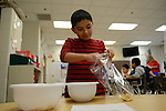 A fifth grader in Ms. Heidy's class measures out proportions to make granola as part of the small bites program which encourages healthy eating at the Nathanael Greene Elementary School in the McKinley Park neighborhood of Chicago, Illinois on December 19, 2014.  All but one of Ms. Heidy's student receives food assistance through the Supplemental Nutritional Assistance Program or SNAP,  which includes a free school lunch.