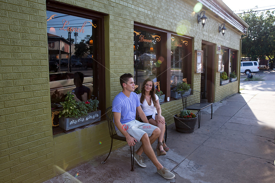 Young attractive couple people watches while sitting on a bench in the vibrant Eastside, East Sixth Street, bar and restaurant entertainment scene in East Austin.