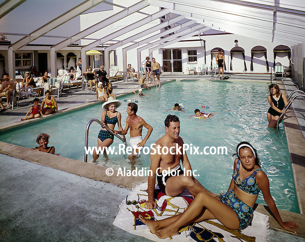 Couples enjoying the Carrilion Motel's inddor / outdoor pool. Located in Atlantic City. 1960's photograph.