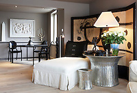 A large painted screen behind a contemporary daybed has a matching silver-paintedl table and stool to one side
