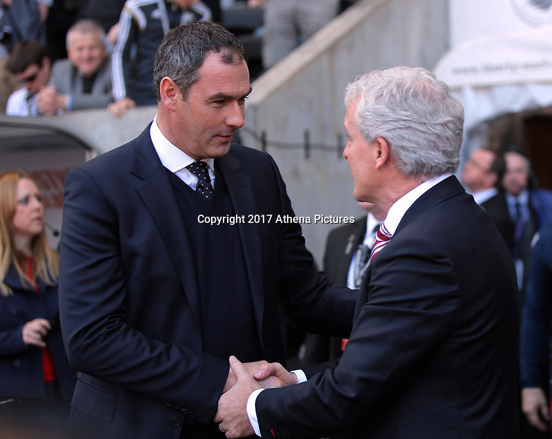 SWANSEA, WALES - APRIL 22: (L-R) Manager of Swansea City, Paul Clement greets manager of Stoke City Mark Hughes  in the dug out during the Premier League match between Swansea City and Stoke City at The Liberty Stadium on April 22, 2017 in Swansea, Wales. (Photo by Athena Pictures/Getty Images)