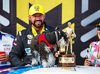 Oct 30, 2016; Las Vegas, NV, USA; NHRA pro stock driver Shane Gray celebrates with the family dog and his Wally trophy after winning the Toyota Nationals at The Strip at Las Vegas Motor Speedway. Mandatory Credit: Mark J. Rebilas-USA TODAY Sports