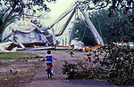 A child rides his bike in front of the fallen water tower in Apalachicola, Florida after Hurricane Kate plowed through Apalachicola, Florida November 21, 1985.  Kate, a late November Hurricane,  was latest forming Atlantic hurricane on record at the time and was the second for the area following Hurricane Elena two months earlier.