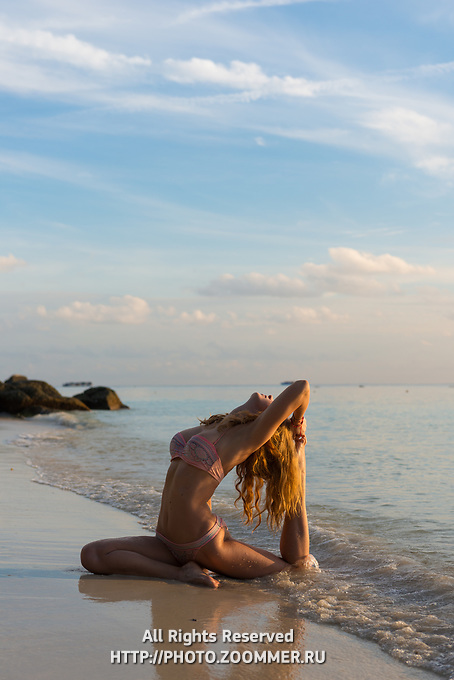 Beach yoga in Ko Lipe island Thailand, girl in pigeon pose
