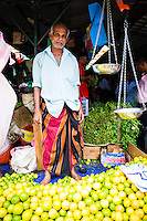 Man selling limes at his market stall in Kandy market, Kandy, Central Province, Sri Lanka Highlands, Asia. This is a photo of a man selling limes at his market stall in Kandy market, Kandy, Central Province, Sri Lanka Highlands, Asia.