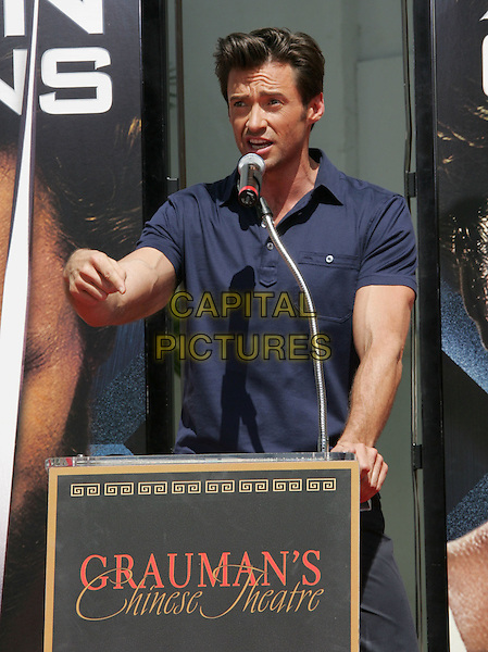HUGH JACKMAN .Handprint And Footprint Ceremony Honoring Hugh Jackman held at Grauman's Chinese Theatre, Hollywood, California, USA..April 21st, 2009.half length blue top microphone speech podium hand pointing veins .CAP/ADM/MJ.©Michael Jade/AdMedia/Capital Pictures.