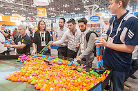 Visitors shoot foam balls in Hogwild's booth with power poppers at the 114th North American International Toy Fair in the Jacob Javits Convention center in New York on Sunday, February 19, 2017.  The four day trade show with over 1000 exhibitors connects buyers and sellers and draws tens of thousands of attendees.  The toy industry generates over $26 billion in the U.S. alone and Toy Fair is the largest toy trade show in the Western Hemisphere. (© Richard B. Levine)