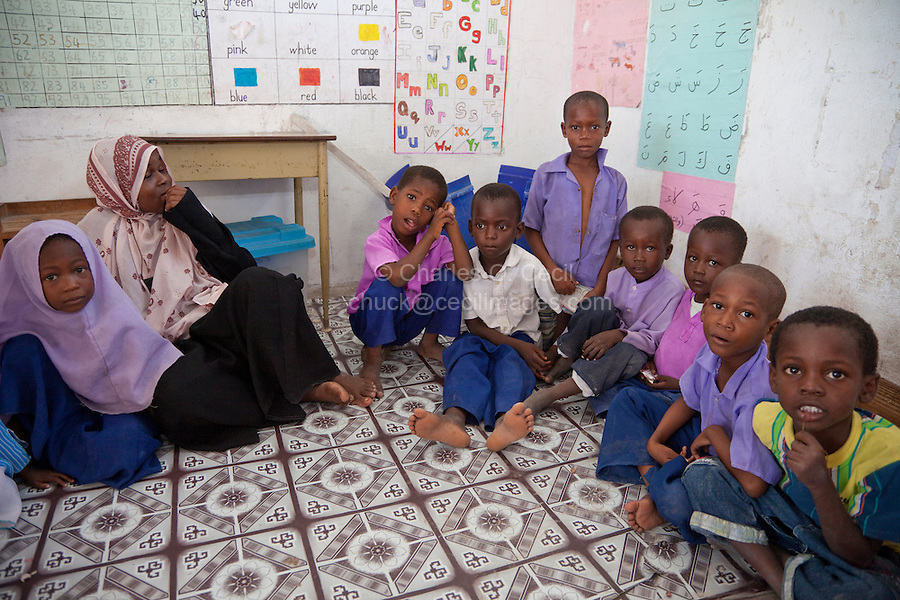 Jambiani, Zanzibar, Tanzania.  Primary School Classroom and Schoolchildren.  The classroom has no furniture; students and teacher sit on the floor.  Materials on the wall show that the children are learning to read both the Arabic and the Latin alphabets.  They learn Arabic to read the Koran.  Both English and Swahili use the Latin alphabet.  English is the language of higher education in Tanzania, and of the courts.