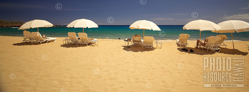 Beach-goers enjoy a sunny day under big, shady umbrellas at Hulopo'e Beach, Lana'i.