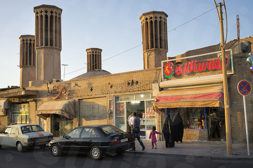 June 22, 2014 - Yazd (Iran). Locals walks past a building with typical wind towers installed on the roof. The towers are a traditional Persian architectural element used to create natural ventilation in buildings. © Thomas Cristofoletti / Ruom