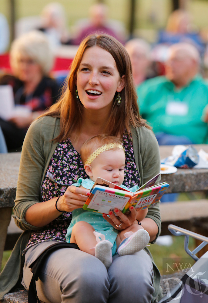 NWA Democrat-Gazette/DAVID GOTTSCHALK  Carolyn Wilcox holds her daughter Etta, 8 months, Monday, September 28, 2015 as she sings during Gather at the River, a celebration at Bunch Park in Elkins. The event took place over three nights sharing a message, music and community.