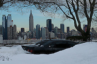 A car is covered with snow at the neighborhood of Weehawken while the Empire State Building and Middle Manhattan are seen on the background after the pass of the winter storm JONAS, in New York, 01/24/2016. Photo by VIEWpress