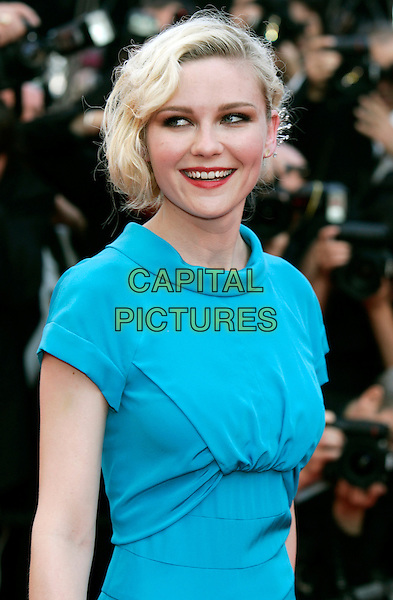 KIRSTEN DUNST.Attending the Palme d'Or Closing Ceremony held at the Palais des Festivals during the 63rd Annual International Cannes Film Festival,.Cannes, France, May 23rd, 2010.half length blue turquoise dress round neck cap sleeve red lipstick make-up  smiling .CAP/PE.©Peter Eden/Capital Pictures.