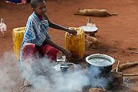TANZANIA, Korogwe, Massai in Kwalukonge village, women boil water/ TANSANIA, Korogwe, Massai im Dorf Kwalukonge, Frau kochen Wasser