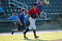 A young baseball player takes the field with Kannapolis Intimidators third baseman Zach Remillard (8) prior to the game against the Hagerstown Suns at Kannapolis Intimidators Stadium on June 15, 2017 in Kannapolis, North Carolina.  The Intimidators defeated the Suns 9-1 in game two of a double-header.  (Brian Westerholt/Four Seam Images)