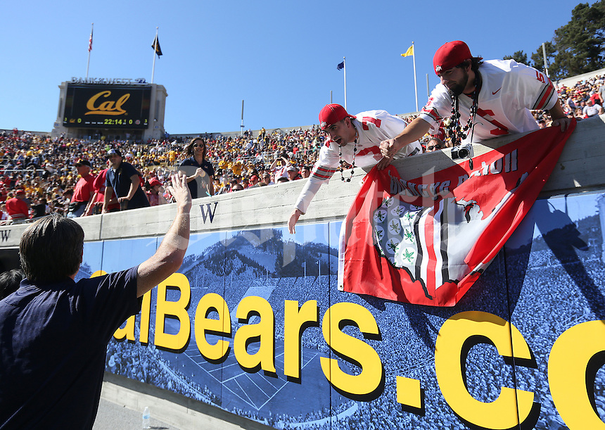 Twin Ohio State fans Jeff, right, and Zach Edgington, 27, from Columbus try to high five a California fan prior to the NCAA football game at Memorial Stadium in Berkeley, California on Sept. 14, 2013. (Adam Cairns / The Columbus Dispatch)