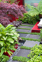 Japanese maple Acer palmatum in raised bed garden with water feature, stones, Heuchera, ferns in burgundy red and green color theme tones, stone wall, in Asian Japanese style garden