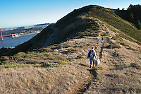 Volunteers Nick Villa and Ann Rugger head down the trail from the bird blind in the Marin Headlands at the end of a typically long day of bird banding for the Golden Gate Raptor Observatory.