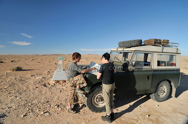 Africa, Tunisia, between Matmata and Kebili. Desert travellers Kerstin and Doris reading the map on the bonnet of their historic 1962 Land Rover Series 2a.  --- No releases available, but releases may not be needed for certain uses. Automotive trademarks are the property of the trademark holder, authorization may be needed for some uses.  --- Info: Image belongs to a series of photographs taken on a journey to southern Tunisia in North Africa in October 2010. The trip was undertaken by 10 people driving 5 historic Series Land Rover vehicles from the 1960's and 1970's. Most of the journey's time was spent in the Sahara desert, especially in the area around Douz, Tembaine, Ksar Ghilane on the eastern edge of the Grand Erg Oriental.