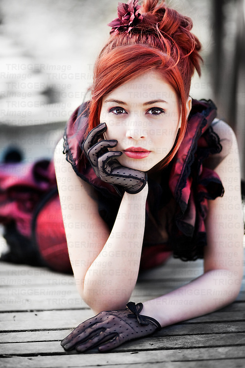 Redhead dressed in Victorian style laying on a wooden bridge