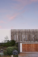 A discreet, environmentally aware beach house. The façade is punctuated by irregularly patterned American Redwood cladding, which heightens the sense of the house being at one with nature and functions as both a sunscreen and a decorative element.