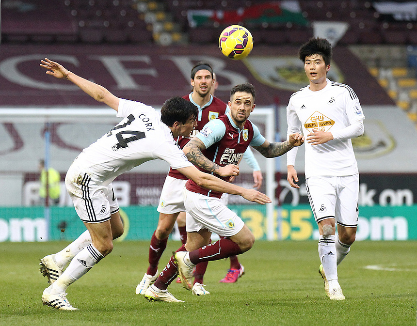 Swansea City's Jack Cork and Burnley's Danny Ings vie for possession of an aerial ball<br /> <br /> Photographer Rich Linley/CameraSport<br /> <br /> Football - Barclays Premiership - Burnley v Swansea City - Friday 27th February 2015 - Turf Moor - Burnley<br /> <br /> &copy; CameraSport - 43 Linden Ave. Countesthorpe. Leicester. England. LE8 5PG - Tel: +44 (0) 116 277 4147 - admin@camerasport.com - www.camerasport.com