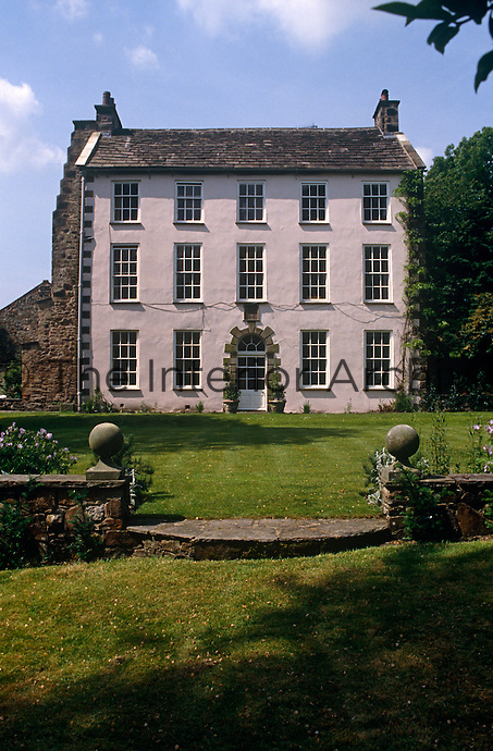 The brick facade of this four-storey Georgian rectory has been rendered and the rows of sash windows are unusual for such an early 18th century country house