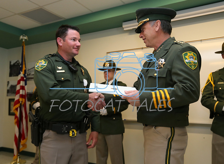 Carson City Sheriff Kenny Furlong, right, presents Deputy John Hitch with a life-saving award during a ceremony at the Carson City Sheriff's Office in Carson City, Nev., on Wednesday, April 24, 2013. .Photo by Cathleen Allison