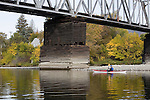 Elliot Scull paddling Current Designs kayak under railroad bridge on the lower Wenatchee River in fall.  Wenatchee, Washington