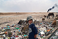 Baghdad, Iraq, June 13, 2003.Ahmed a young shepherd, leads his flock through the garbage surrounding Saddam City, a cracked Iraqi Army helmet on his head.