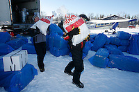 Volunteer load handlers move, sort and stack musher's food bags at the Willow airport during the first day of flying straw, musher's dog food bags and people food & gear out to checkpoints south of the Alaska Range.  Saturday Feb. 21, 2009  Iditarod 2009