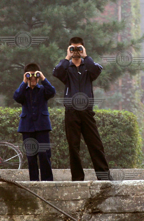 Youths use binoculars to look out onto the Amrok (Yalu) River, which marks the border between North Korea and China.