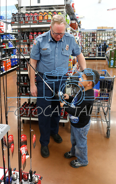 David Bourne, with East Fork Fire, shops with Ryan, 7, at the 15th annual Holiday with a Hero program at Walmart in Carson City, on Wednesday, Dec. 19, 2018. The program, which pairs local heroes with more than 200 K-8th graders, provides a $100 Christmas shopping spree at Walmart.  <br /> Photo by Cathleen Allison/Nevada Momentum