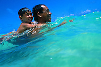 Local father and son playing in ocean, Windward Oahu